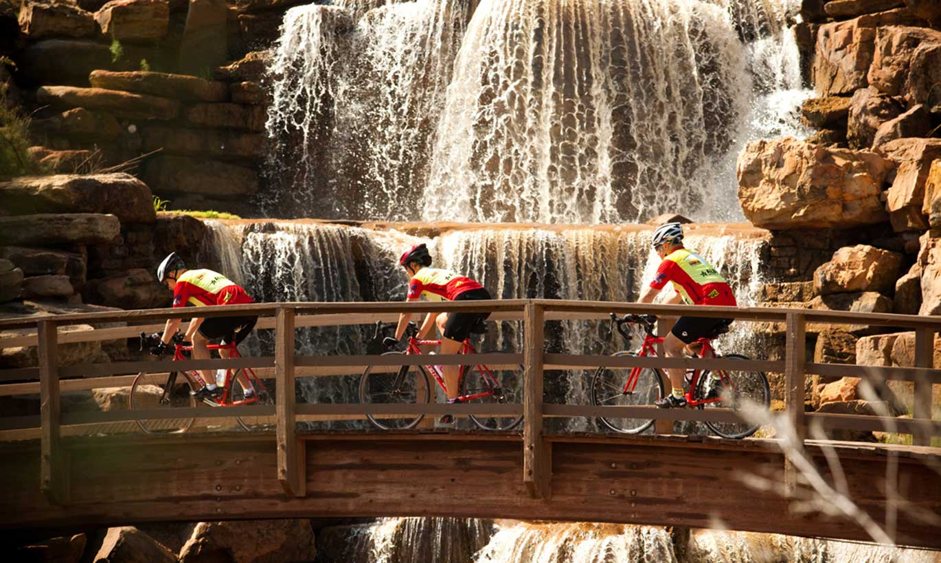 Three cyclists bike over a bridge in front of a waterfall in Wichita Falls, Texas.