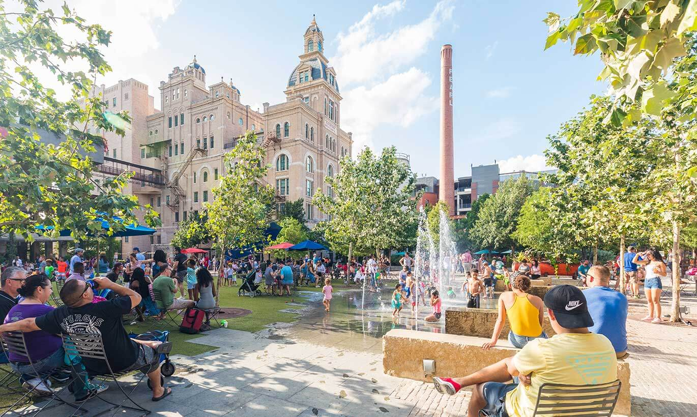 Groups of people gather in a courtyard and lawn space and children play in a fountain outside of Pearl Brewery in San Antonio, Texas.