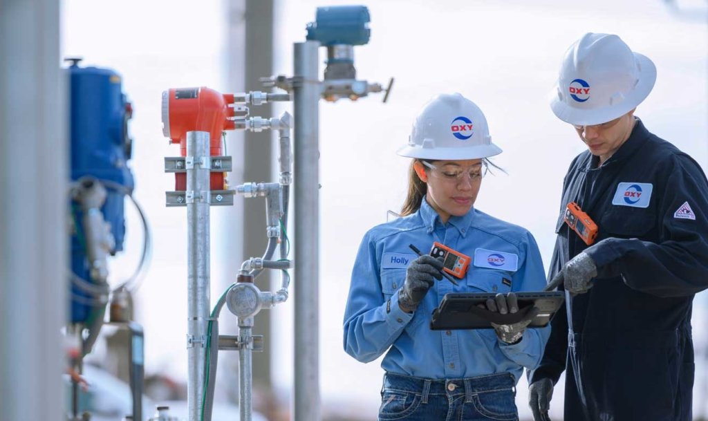 Two Occidental workers wearing hard hats work out in the field with a tablet next to industrial equipment.
