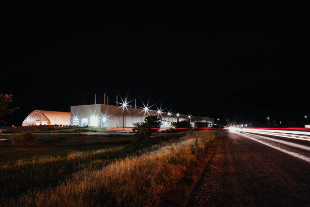 Cars on a highway drive past a large industrial facility lit up at night in Abilene, Texas.