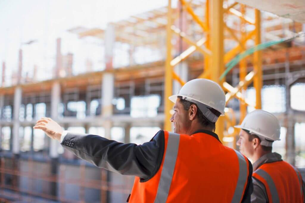 Two men in hard hats and orange safety vests gesture toward their work site.