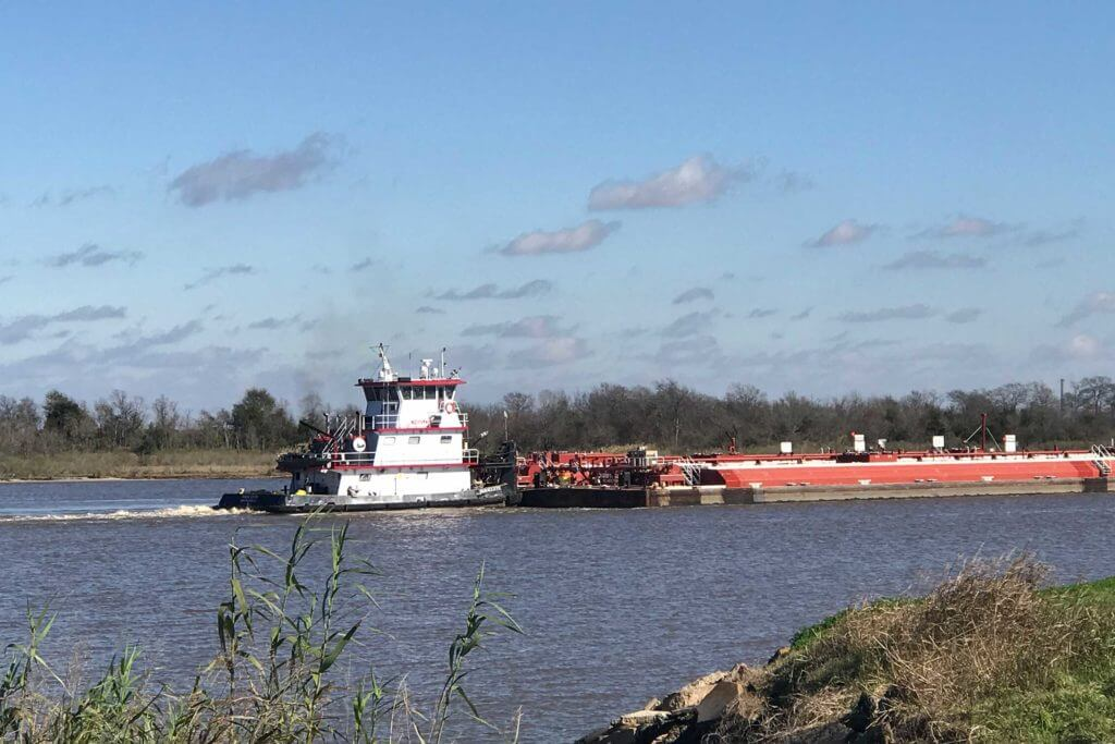 A large cargo ship floats down the river at Port Arthur, Texas.