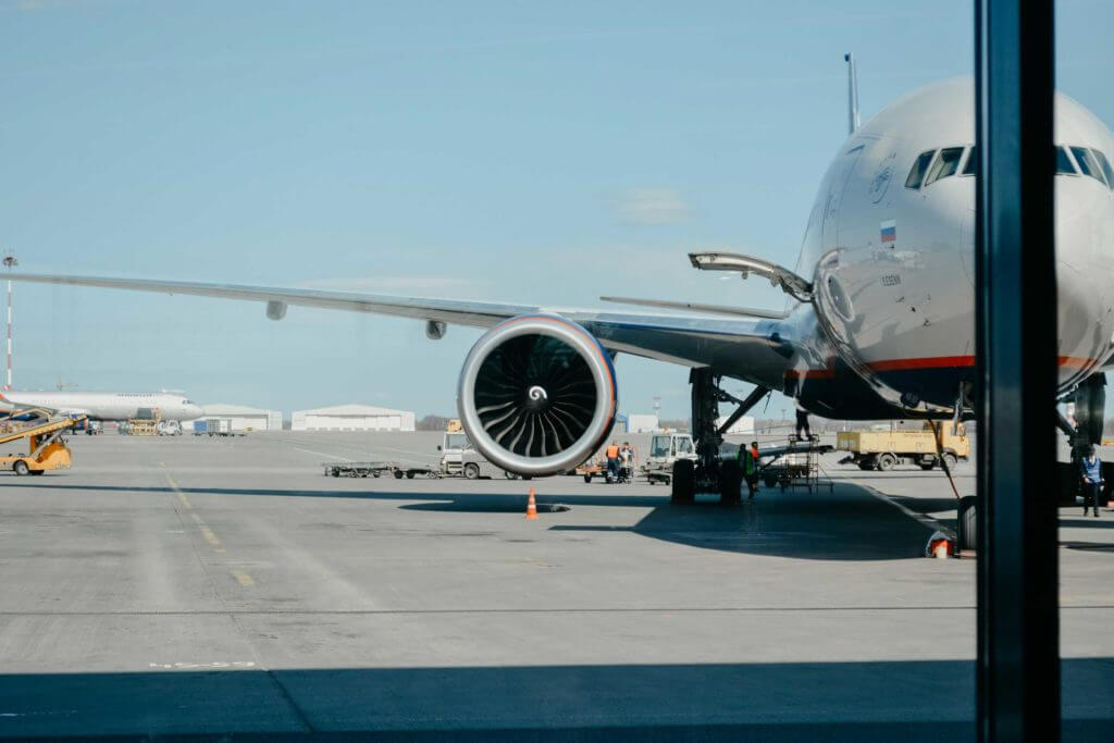 The turbine of an airplane is in focus while the plane is loaded before take off