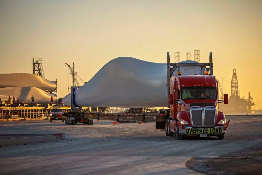 A large truck transports a metal windmill propellor at the Port of Brownsville, Texas.