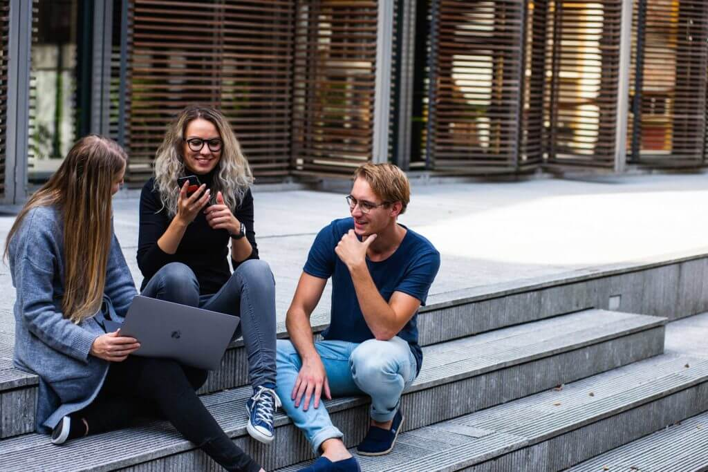 Three college students sit outside on the steps of a building with their laptops.