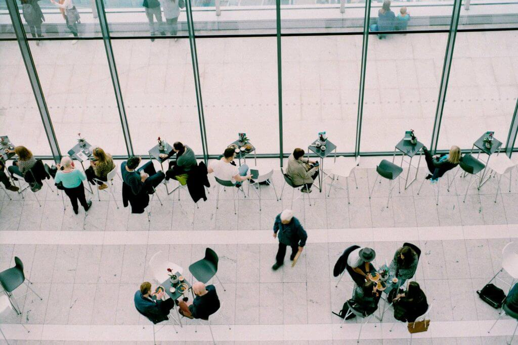 Overhead shot of a downstairs cafe where people can be seen eating, networking, and working