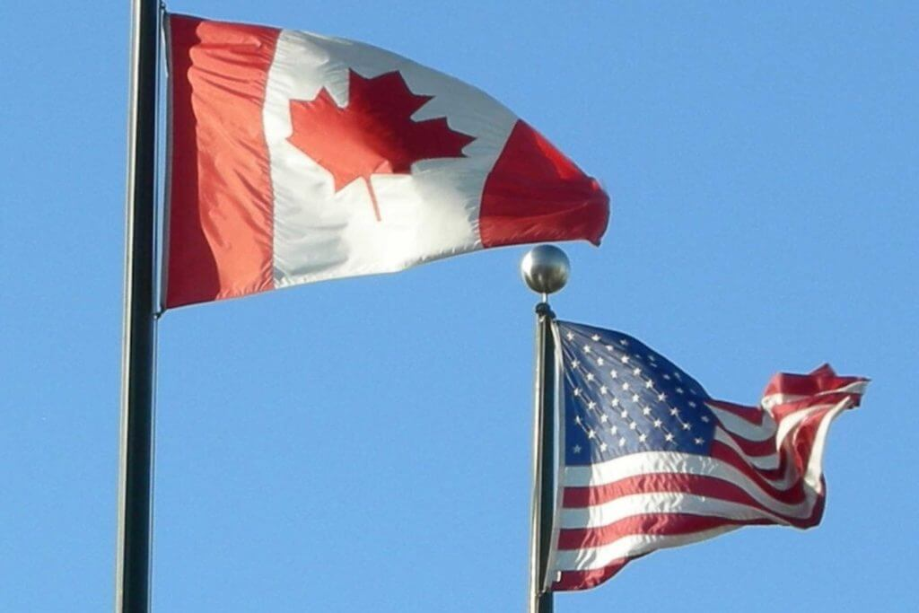 The US and Canadian flag raised on flagpoles
