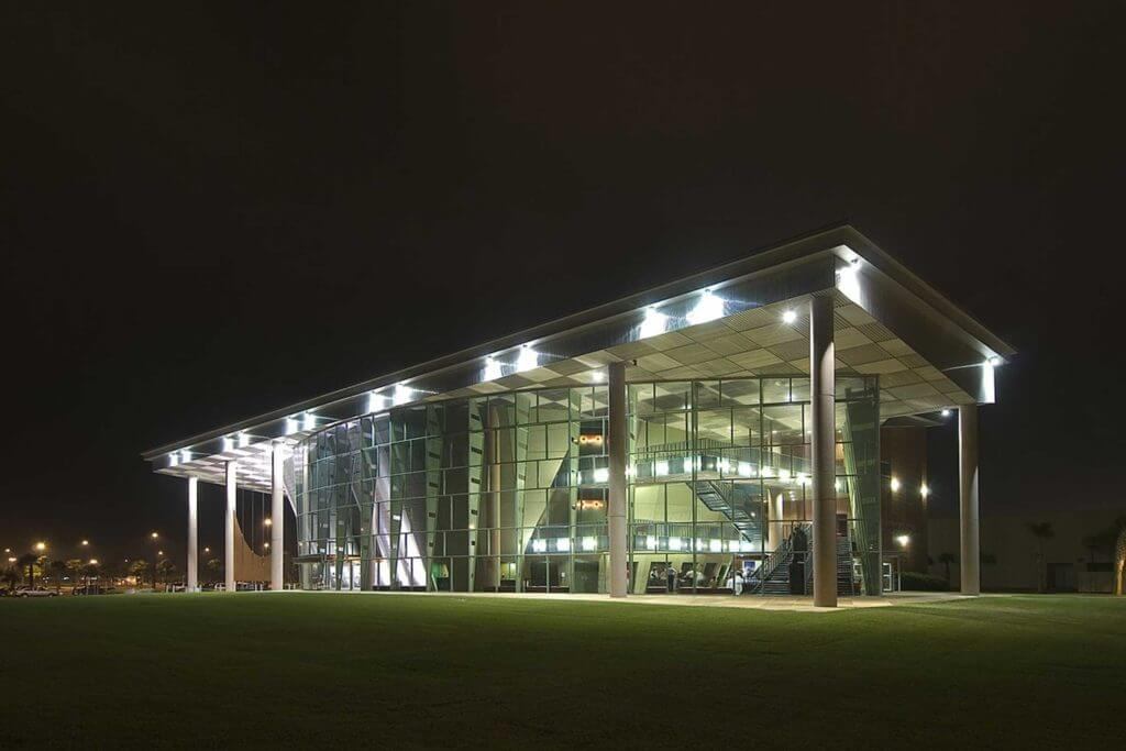 A modern building at Texas A&M University is constructed out of clear glass panels and is lit up at night.