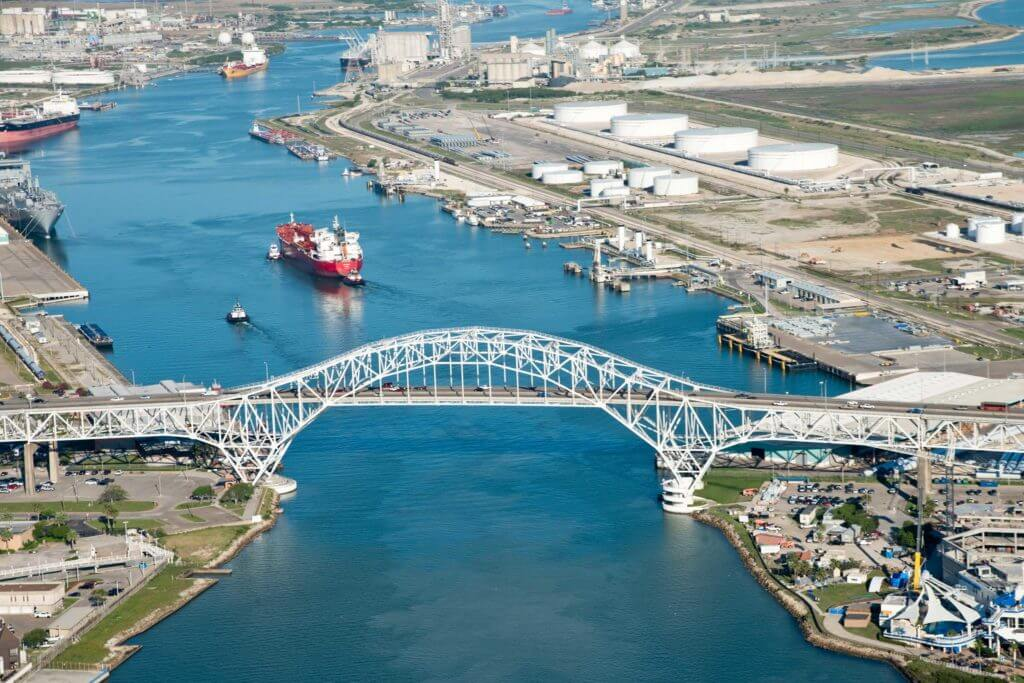 A white bridge at the Port of Corpus Christi stretches over the blue river, and a red cargo ship approaches close to the bridge.
