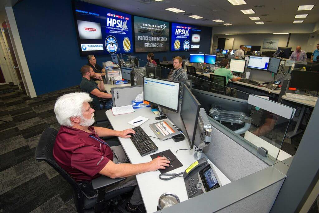 A man with white hair and a white beard concentrates on a computer monitor while working at Lockheed Martin.