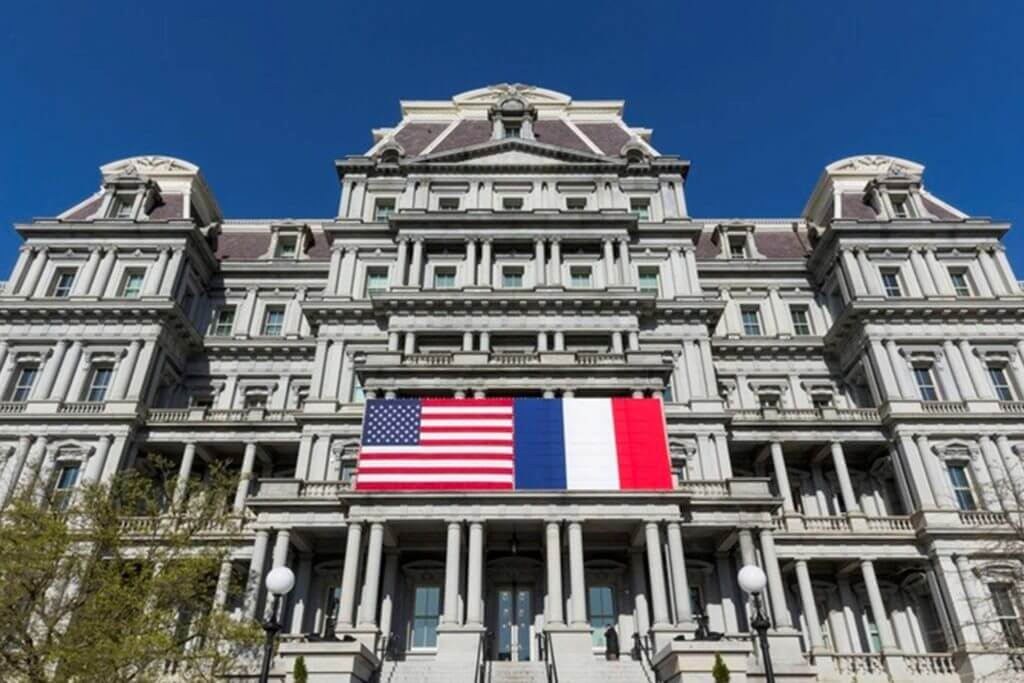 A large building displays the US and French flag