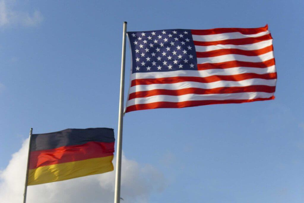 The German and US flag flying in the sky next to each other.
