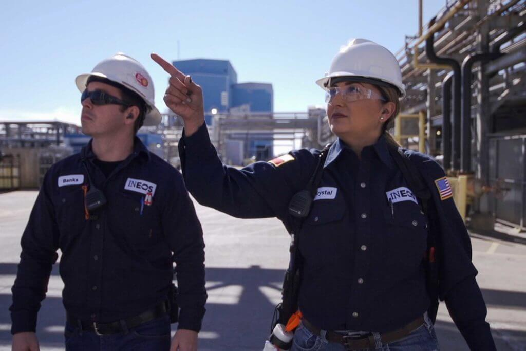 A man and a woman wearing hard hats work in the petrochemical field at INEOS.
