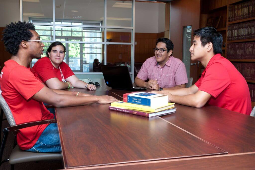 Four students wearing red shirts sit at a table having a discussion at the University of Houston.