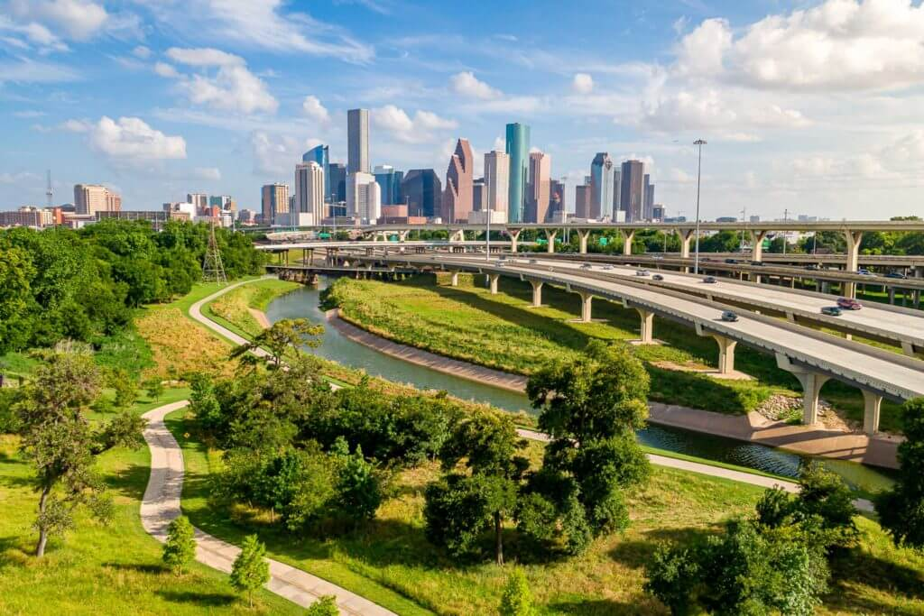 An aerial view of downtown Houston, Texas, with Buffalo Bayou Park and Memorial Drive in the foreground.