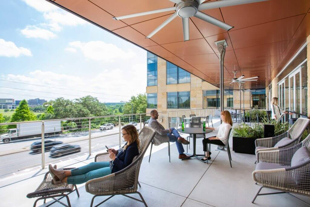 The outdoor patio space of the Silicon Labs office building fills with workers taking their lunch breaks, networking, and enjoying the fresh air in Austin, Texas.