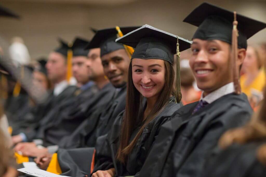 A group of students smile at graduation in Odessa, Texas.
