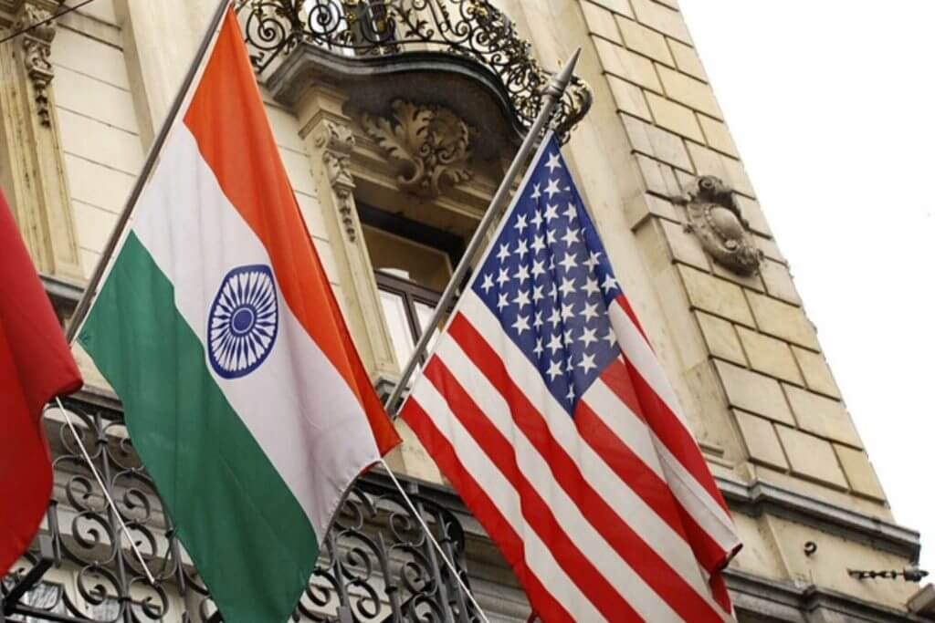 The India and US flag are raised onto a building