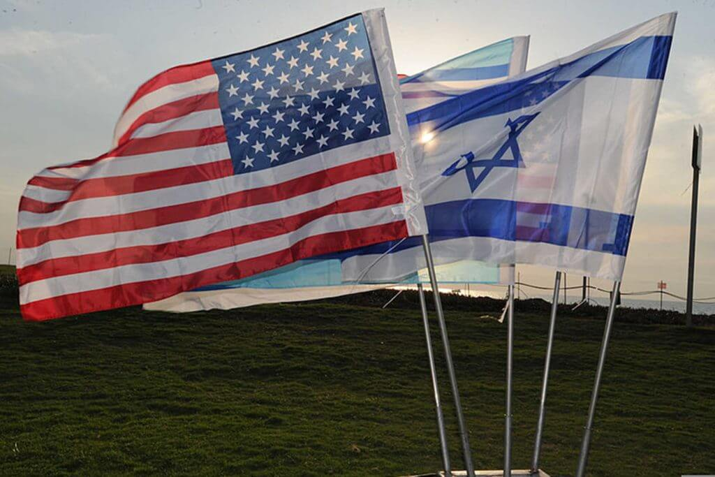 The Israel flag and American flag are flown side-by-side in a field.
