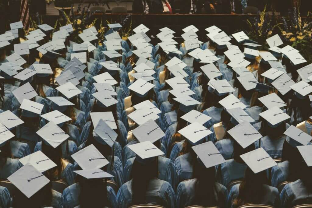 A view looking down at college graduates in their caps and gowns.