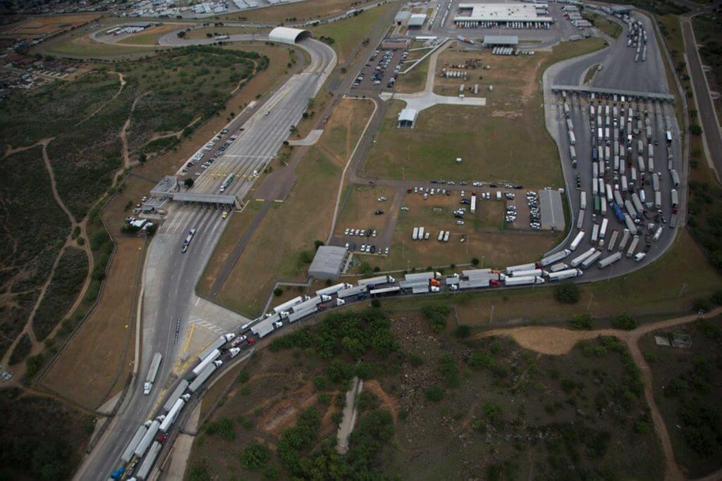Hundreds of trucks lined up on a road pass through a trucking depot.