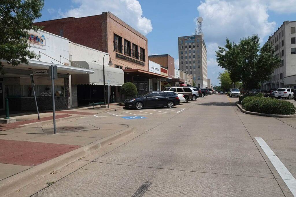 Cars are parked on a street in downtown Longview, Texas.