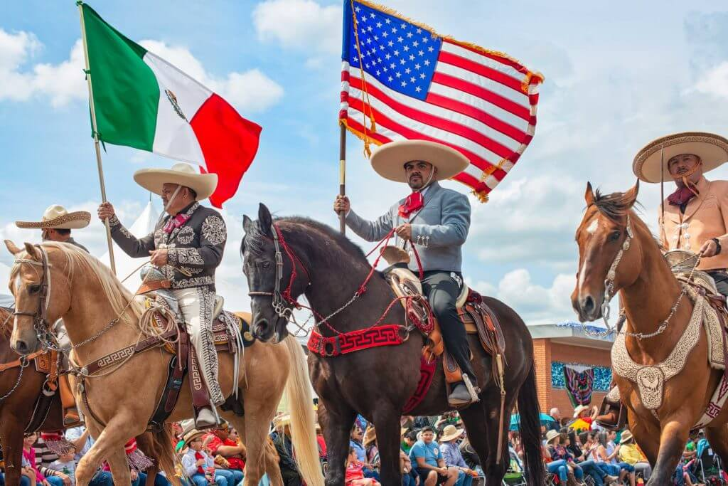 Men mount horses and carry the flags of Mexico and the US as they celebrate Charro Day