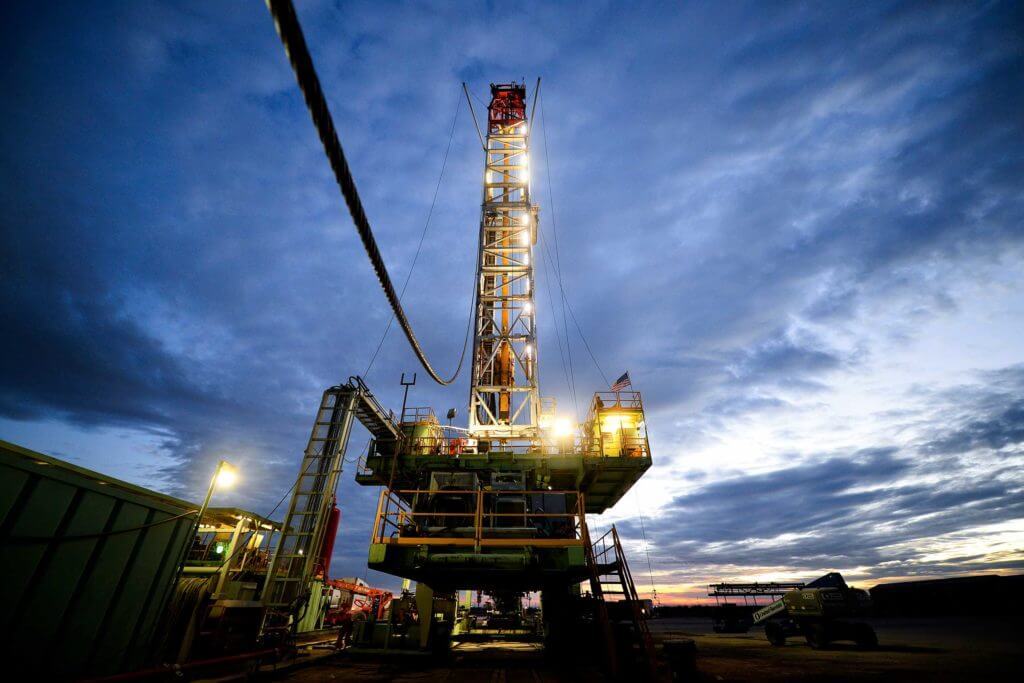 A large green oil rig surrounded by technical equipment is lit up at night in Midland, Texas.