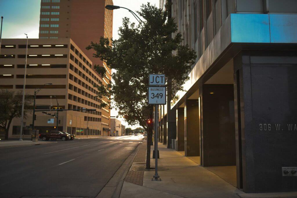 Downtown Midland features large office buildings and a road sign to direct drivers.