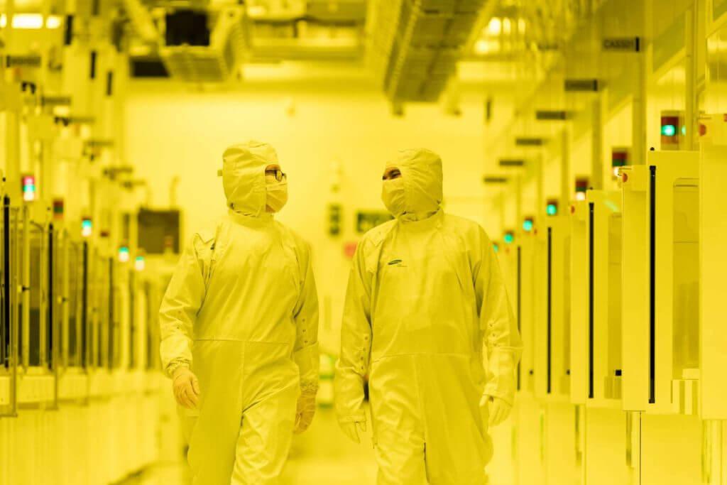 Two people walk down a hallway in hazmat suits