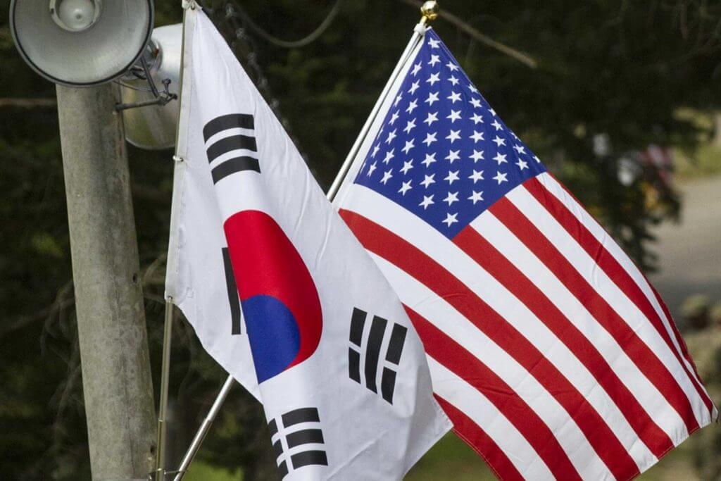 The South Korean flag and US flag hang on a utilities pole