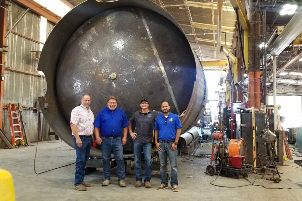 Four men stand in front of a huge metal drum at Wendland Manufacturing facility.