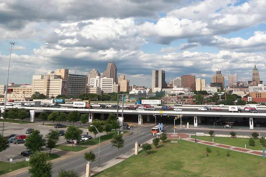 An elevated highway with cars driving on it runs through downtown San Antonio with a view of the city skyline behind it.