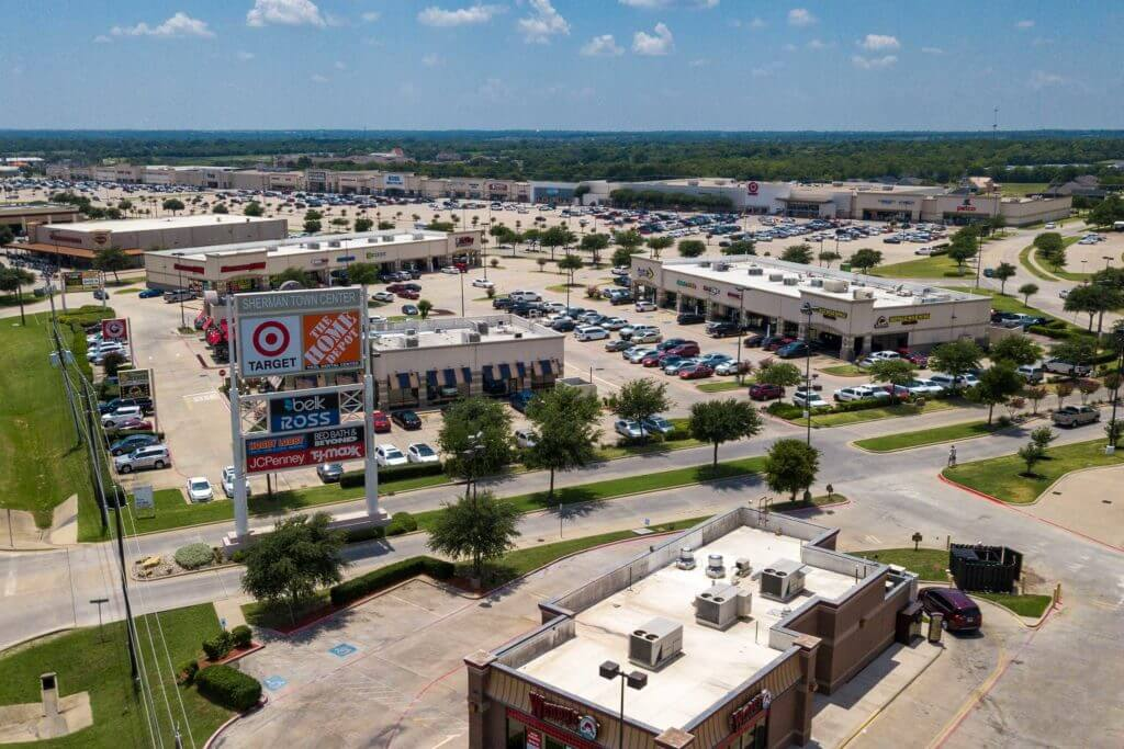 Aerial view of the Town Center in Sherman, Texas with shops and a large parking lot.