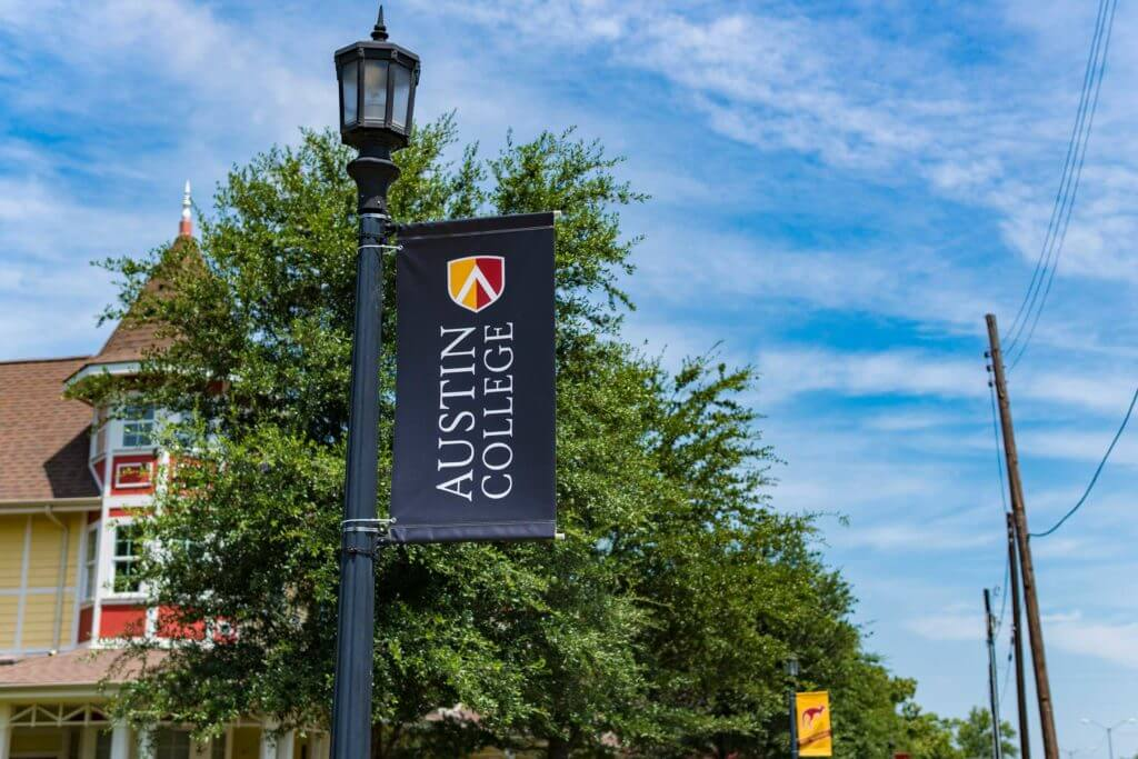 "A banner on a lamppost reads ""Austin College"" with the school's red and yellow logo."