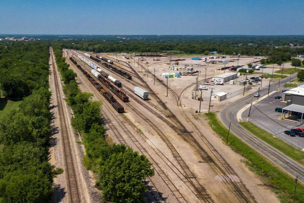 Three trains transport goods down the main railway lines in Sherman, Texas.