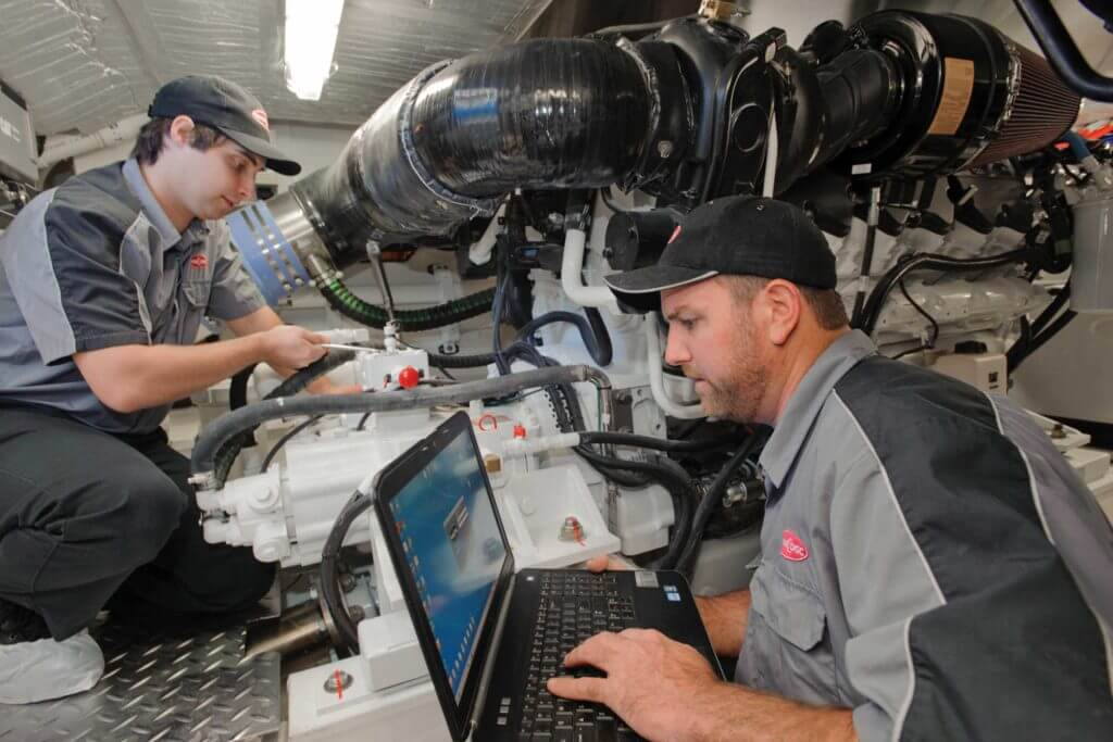 Two workers in gray uniforms use a laptop computer and metal tools to work on a product.