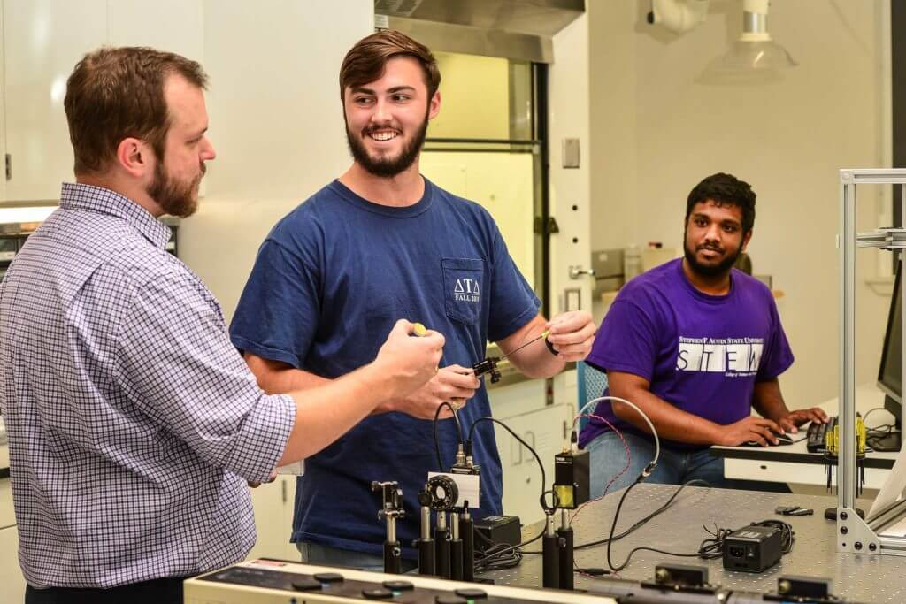 Two STEM students smile while talking to their teacher and working with equipment at Stephen F. Austin State University in Nacogdoches, Texas.