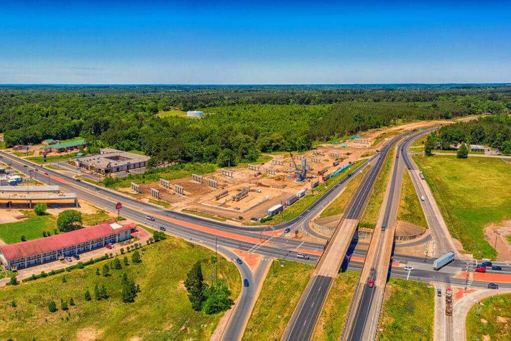 Aerial view of cars driving on a major interstate in Texas Forest Country.