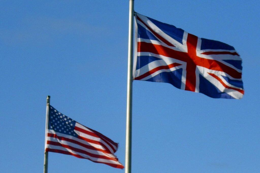 A UK flag and US flag flying in the sky next to each other