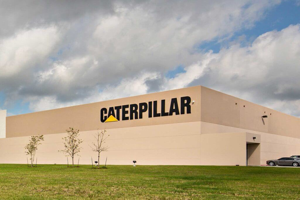Exterior view of the beige concrete Caterpillar manufacturing facility in Victoria, Texas.