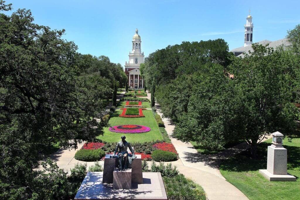 A green lawn with colorful flowers sits in front of Pat Neff Hall at Baylor University in Waco, Texas.