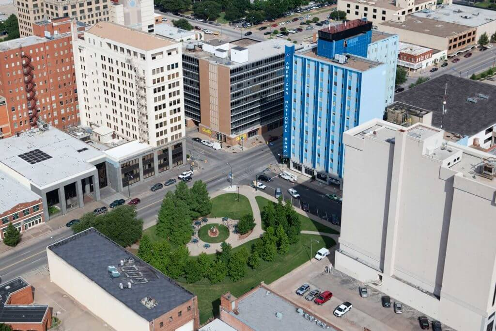 A view of downtown Wichita Falls, with local businesses including American National Bank, surrounding a small park.