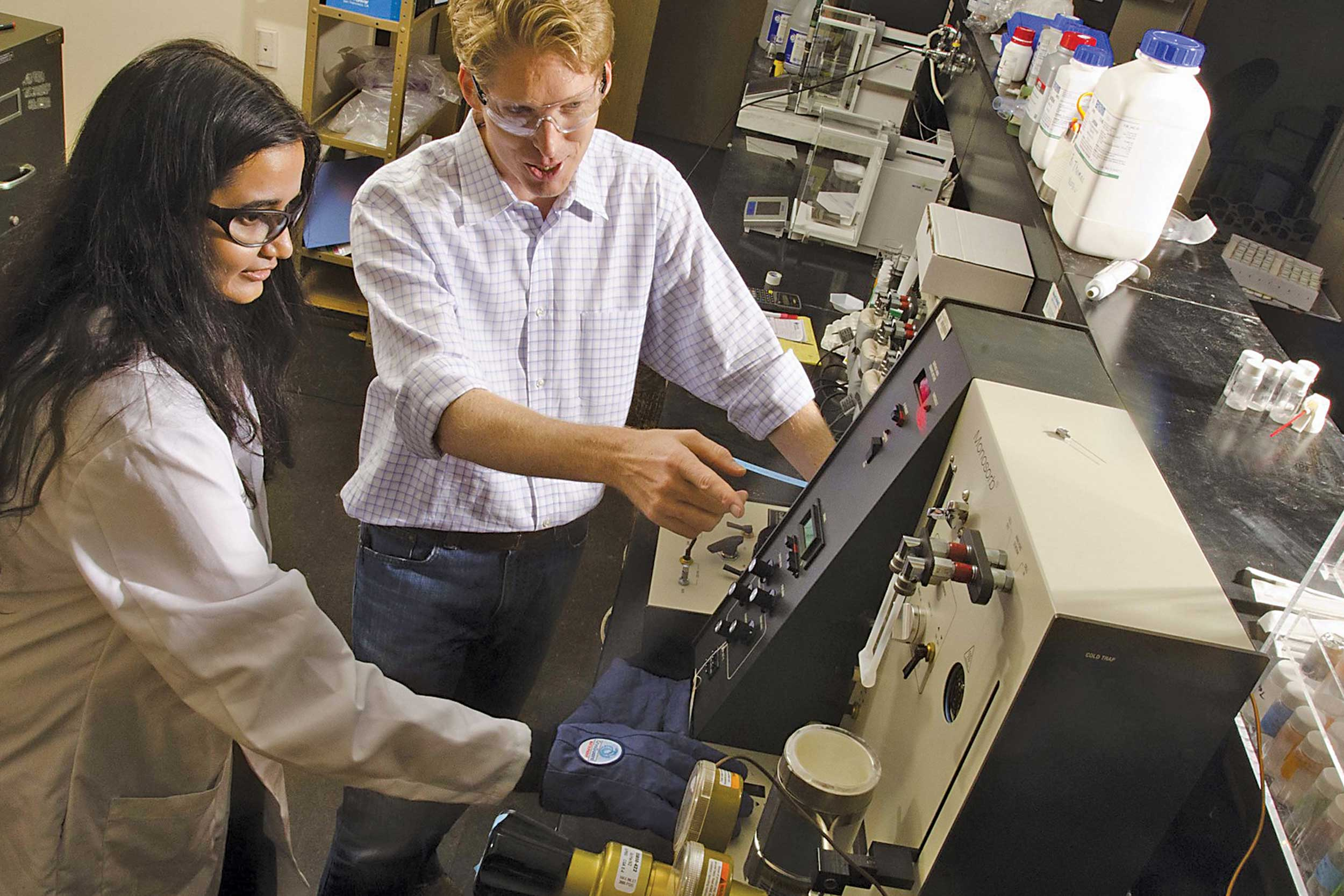 A professor assists a student with machinery in a University of Texas lab.