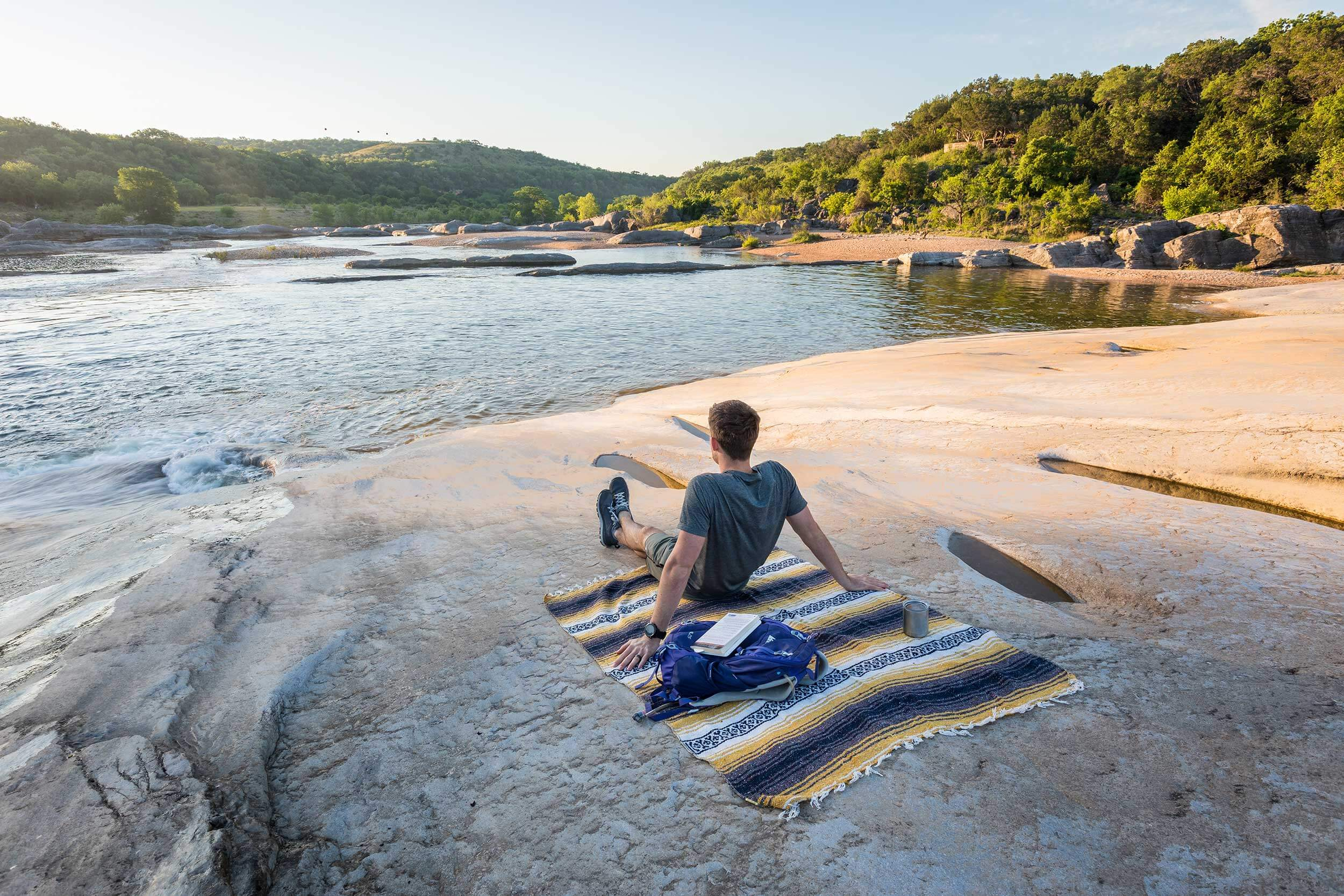 A man sits on a blanket and gazes out at the water in Pedernales Falls State Park, Texas.