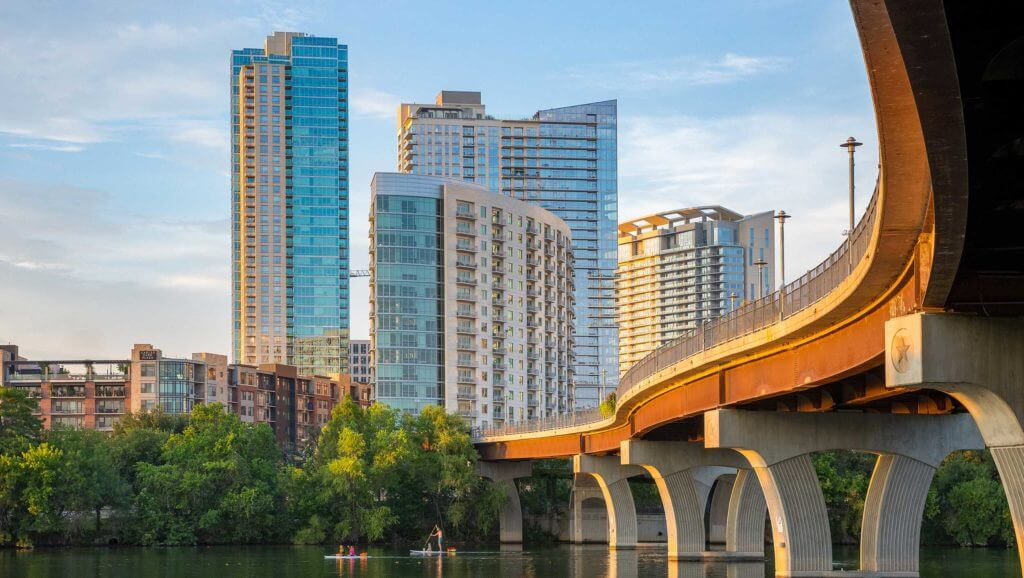 Highrise buildings look over a riverfront, where a family can be seen paddleboarding under a large bridge running across in Texas.