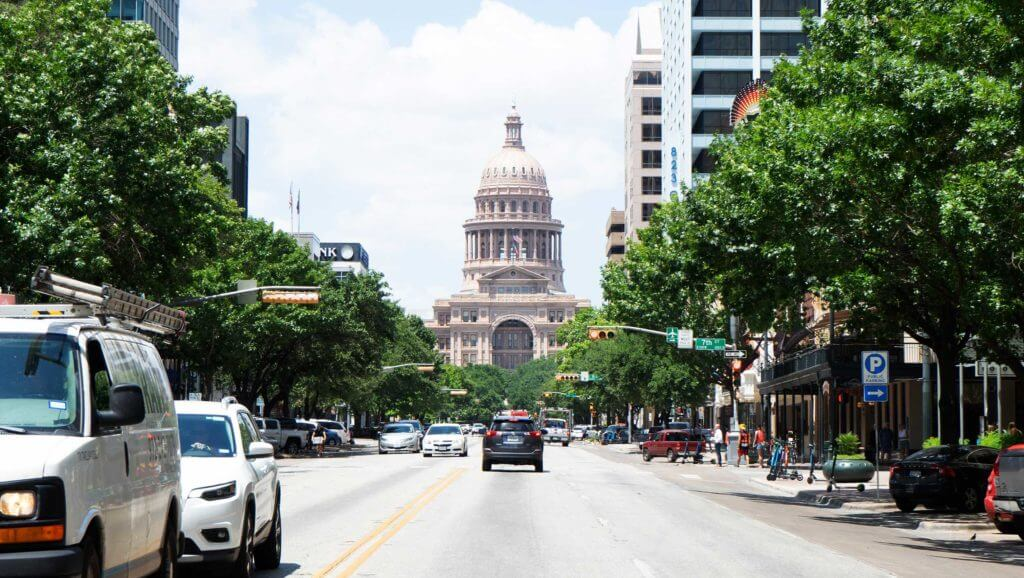 A busy street approaches the Texas Capital building in Austin, Texas.