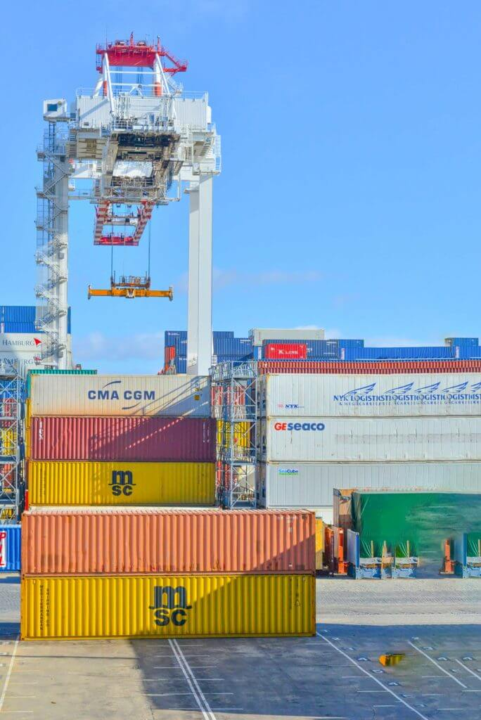 Multiple shipping cargo boxes are stacked on top of each other at a port.