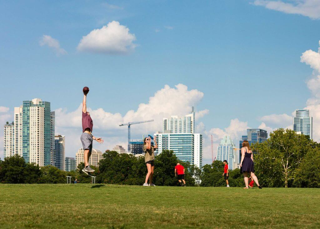 A group of friends gather at Zilker Park to throw a football in Austin, Texas