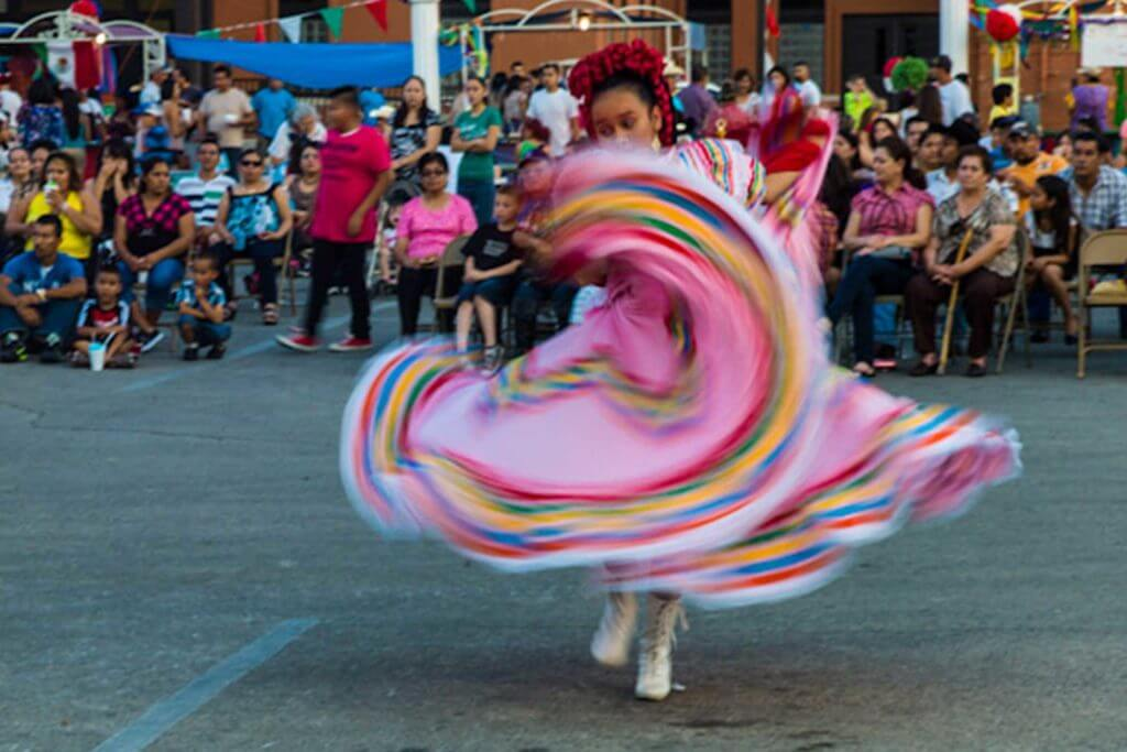 A woman dances in a traditional Mexican dress on Cinco De Mayo in Texas